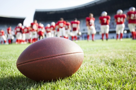 Photo: Cose Up Of An American Football On The Field, Players In The Background